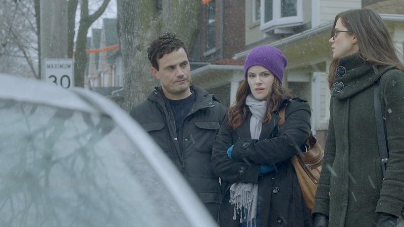 A man and two women stand outside, dressed for winter.