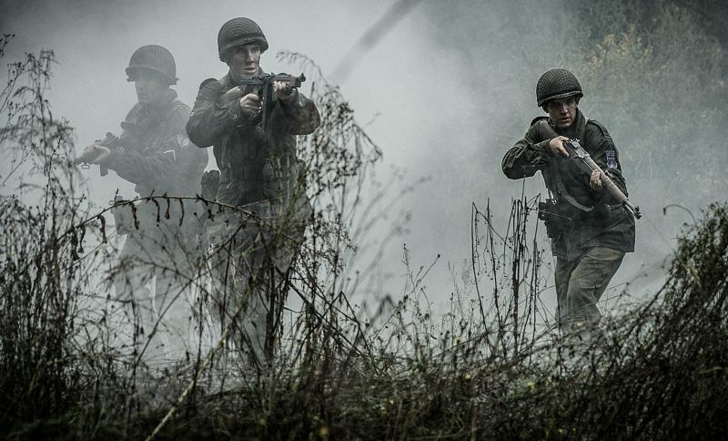 Three soldiers walk across a field