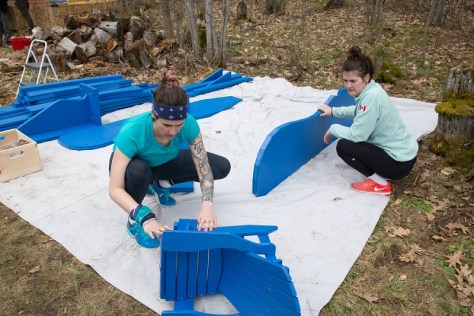 Two women build a chair.
