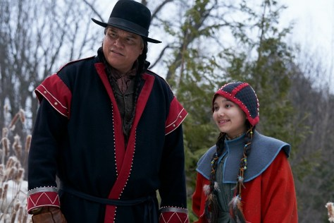 A First Nations man and girl smile into the camera.