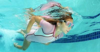 Criança na piscina usando tampão de ouvido
