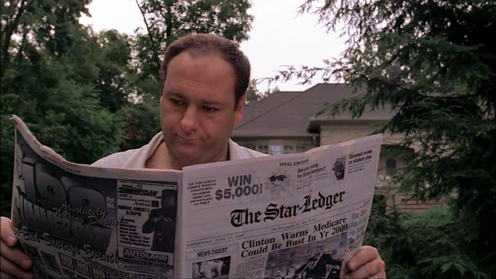 tony soprano is picking up the paper on his driveway and opening it to read it.