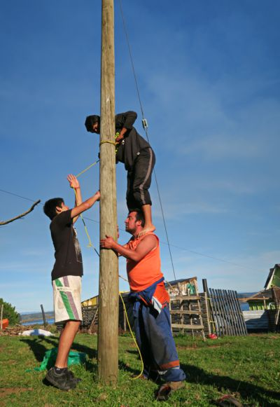 Human pyramid tying a rope to a pole