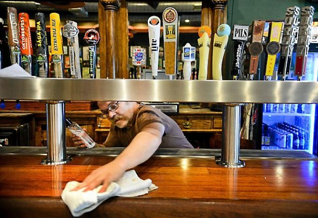 "Bartender Felix Jones oils the newly installed bar at the renovated Turf Club on University Avenue in St. Paul on Wednesday, August 27, 2014. ""I will wipe this bar down thousands and thousands of times, but this time will always be my favorite,"" he said. (Pioneer Press: Ben Garvin)"