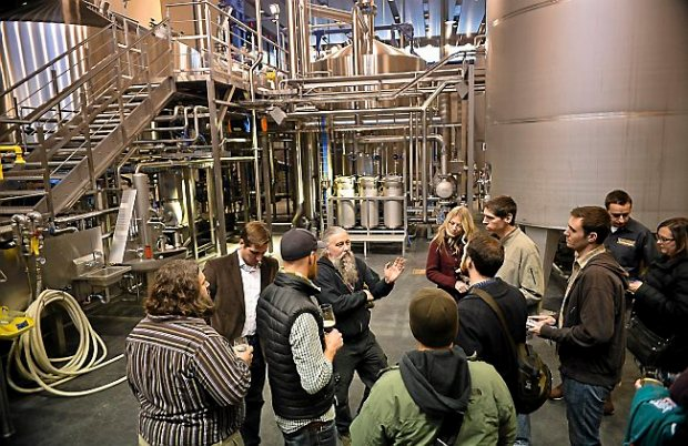 Surly brewmaster Todd Haug, center with beard, explains the technical details behind the company's new $30 million destination brewery in Minneapolis on Thursday, December 18, 2014. The company has ambitions of circulating its beer, which is currently available only in Minnesota and Chicago, to the larger Midwest.(Pioneer Press: Ben Garvin)