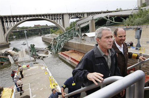 President Bush, left, is accompanied by Hennepin County Sheriff Richard Stanek, right, as he tours the damage at the collapsed Interstate 35W bridge over the Mississippi River Saturday. (AP Photo/Charles Dharapak)