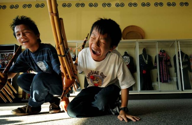 "Seventh-grader Leng Lee, center, laughs with Khamsaeng Xiong, left, while learning to play the ""qeej,"" a wind instrument, as part of an after-school enrichment program at the Community School of Excellence, a Hmong charter school, in St. Paul in 2010. (Pioneer Press: Richard Marshall)"