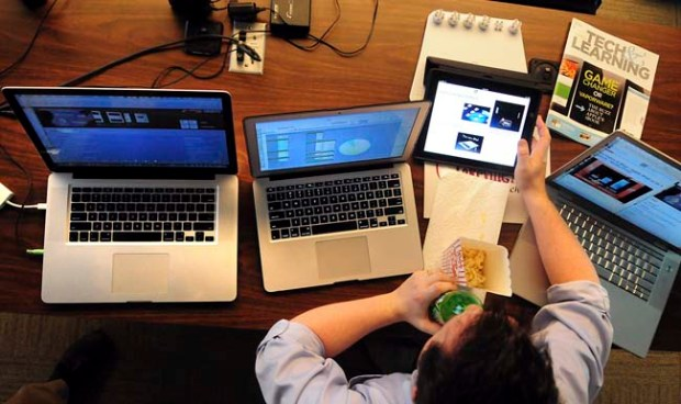 Lakeville school administrator Jason Molesky (with assessment and accountability) monitors three Apple computers and an iPad as news of Apple's new iPad is live blogged by various tech websites at the Lakeville School District offices in Lakeville, Minn., on Wednesday, March 7, 2012. (Pioneer Press: Ben Garvin)