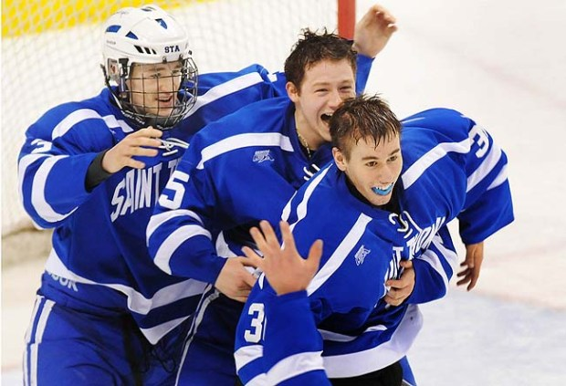 St. Thomas Academy goalie David Zevnik, right, is hugged by teammate Eric Schurhamer, middle and T.J. Samec left, as time expires on their Minnesota State Class A chamionship victory, a 5-1 win over Hermantown, at Xcel Energy Center in St. Paul on Saturday March 10, 2012. (Pioneer Press: Richard Marshall)