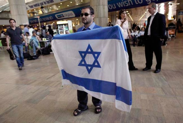 An activist holds an Israeli flag in protest against a pro-Palestinian campaign expected to arrive at Ben B=Gurion Airport near Tel Aviv, Israel, on Sunday. Israel deployed hundreds of police at its main airport to detain activists flying in to protest the country's occupation of Palestinian areas, defying vigorous Israeli government efforts to block their arrival.