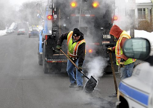 Street Service Worker Brian Cook, left, fills a pothole on Third Street on the city's East Side, Friday morning, March 4, 2011. On the right is his co-worker Jeremy Bates. (Pioneer Press: Chris Polydoroff)