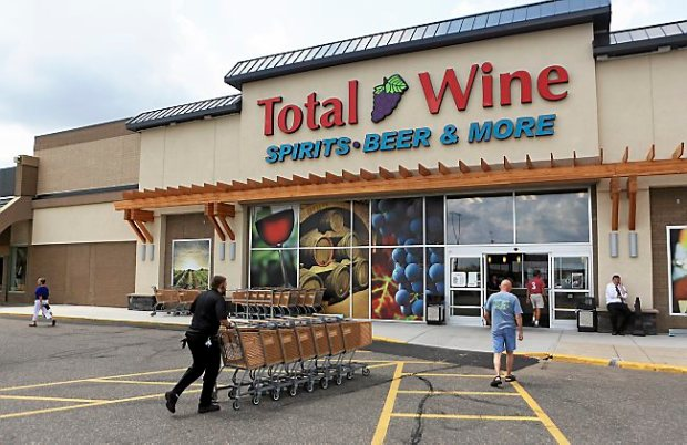 In a July 29, 2014 photo, customers come and go from Total Wine in Roseville. Small liquor stores in Minnesota are facing increased competition from retail giants that offer greater selections, and often lower prices. Maryland-based Total Wine & More and Target are the newest companies seeking to grab a share of the state's alcohol sales, following the footsteps of many grocery chains and big discount retailers. (AP Photo/MPR News, Jeffrey Thompson)