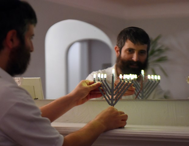 Yitzy Kasowitz places one his Lego Menorahs on the fireplace mantel at his Highland Park home in St. Paul on Wednesday, Dec. 2, 2015. Kasowitz's business, JBlock, produces Jewish-themed Lego sets. (Pioneer Press: John Autey)