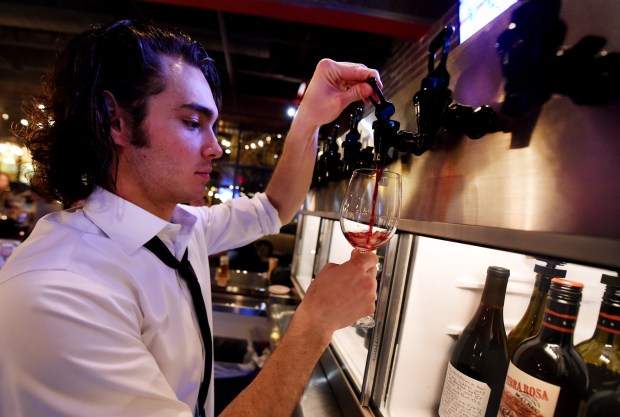 Bartender Michael Senich pours a glass of wine from the wine chiller at the Red Cow in Cathedral Hill in St. Paul on Tuesday, January 19, 2016 (Pioneer Press: John Autey)