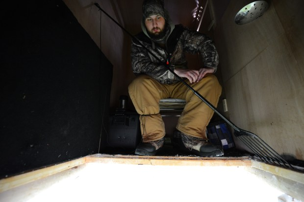 Award-winning fish decoy-carver Eric Wallace of Maple Grove, Minn., looks down a spearing hole through the ice inside his darkhouse on a west metro lake Friday, Jan. 22, 2016. Wallace, 22, hopes to make a living through his business, Wallace Decoys. Darkhouse anglers use decoys to attract certain fish, usually northern pike, and the angler spears them through a large hole in the ice. (Pioneer Press: Dave Orrick)