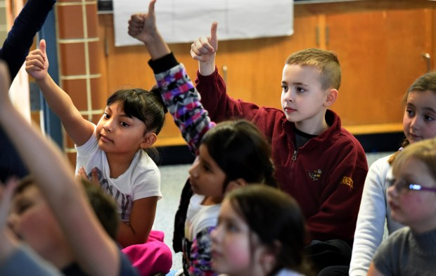 Stephanie Tarrios Sosa, left, and Eli Faulkner give the thumbs-up signal to a teacher to show that they agree and they are on track during a dual language immersion class at Little Canada Elementary School in Little Canada on Thursday, Feb. 11, 2016. Sosa and Faulkner have been paired up by the teacher and work on some projects together. (Pioneer Press: Jean Pieri)
