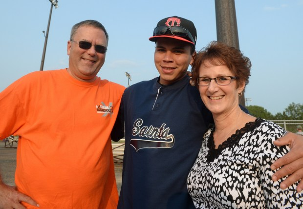 Yordin Alvarez is flanked by Frank Wilcox, left, and Karen Wilcox before his softball game in White Bear Lake on Wednesday, July 30, 2014. (Pioneer Press: John Autey)