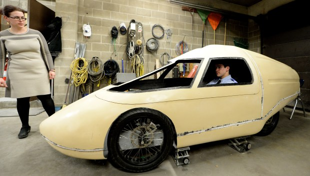 St. Thomas sophomore Joe Zirnhelt tests the seat configuration as St. Thomas French instructor Caroline Little looks on. The St. Thomas's Experimental Vehicle Team is building the car to compete in the Shell Eco-Marathon in Detroit, in April. Photographed in a garage at St. Thomas Academy in Mendota Heights on Tuesday, February 23, 2015. (Pioneer Press: John Autey)