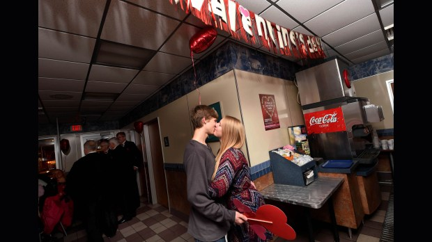 """Anthony Lenzen and Kendra Lundblad kissed after Lundblad surprised her boyfriend, a Chaska High School student, by inviting him to her Park Cottage Grove High School prom, during the Valentine's Day event at White Castle on University Avenue in St. Paul,  February 14, 2016.  It is the 25th year that White Castle has held the special """"Love in the Castle"""" event. (Pioneer Press: Scott Takushi)"""