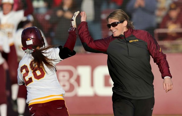 University of Minnesota softball coach Jessica Allister greets Danielle Parlich (28) during a game against Northwestern in Minneapolis on April 10, 2015. Parlich scored three runs in the Gophers 10-5 win. Allister is one of the most successful coaches at the University of Minnesota, guiding her softball team to a national ranking after three straight NCAA tournament appearances. Allister, in her sixth season, has had five straight 30-win seasons, two in a row with 40-plus wins, and is in the midst of a run that could lead to a third 40-win season. Photo courtesy of University of Minnesota Athletics: Eric Miller.