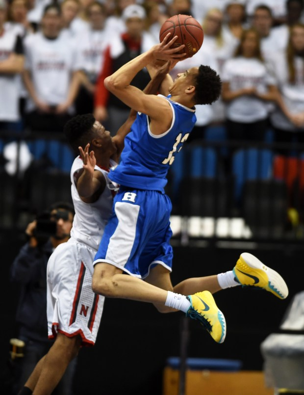 Hopkins' Amir Coffey takes a shot over North St. Paul's Joe Johnson in the first half. (Pioneer Press: Scott Takushi)
