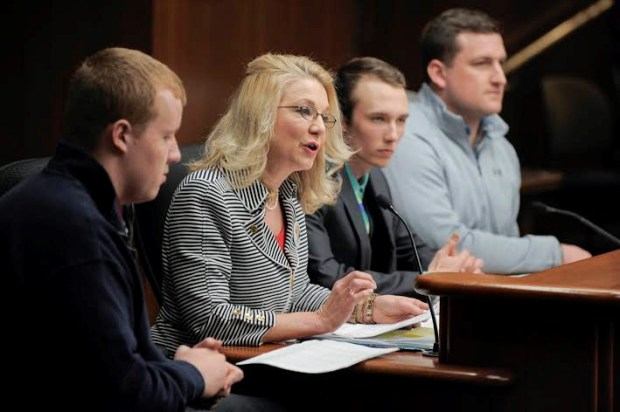 Former Marine Hank Goff, far right, listens as Rep. Cindy Pugh talks about a proposed bill to help mostly veterans who are students to receive emergency dental care compensation at a recent hearing in the Minnesota House of Representatives. Joining Goff are fellow Concordia University (St. Paul) classmates Rick Kelly, far left, and Ryan Olson, to Goff's right. (Courtesy of the Minnesota House of Representatives)