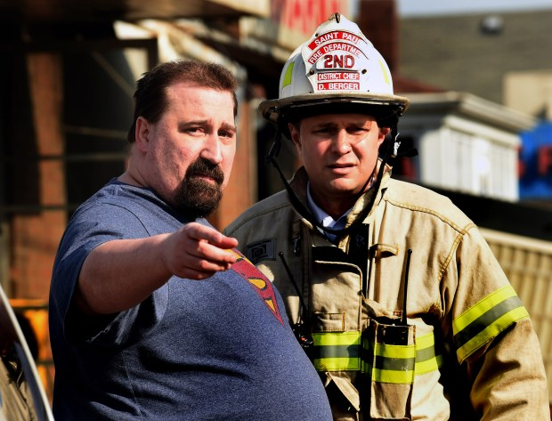 Tim Schmugge, left, who lived on the second floor above Stasny's Food Market with his girlfriend and her children, speaks with District Fire Chief Dave Berger as fire crews make sure the fire is totally out after a fire destroyed the arket on Western Avenue in St. Paul's North End on Thursday, April 14, 2016. (Pioneer Press: Scott Takushi)