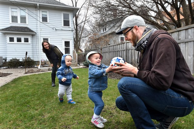 """Wes Burdine and Lydia Garver and their twins, Emil (striped shirt) and Iris, 17 months, moved to this house in Midway in St. Paul last month because of their love for soccer, Friday, April 8, 2016. They are about 10 blocks away from the site of the new Minnesota United FC soccer. Wes is an independent soccer journalist and podcast producer. """"They (the twins) like to kick the ball. They don't understand you can't pick it up,"""" said Lydia Burdine. """"And they like to take the ball from each other."""" (Pioneer Press: Jean Pieri)"""