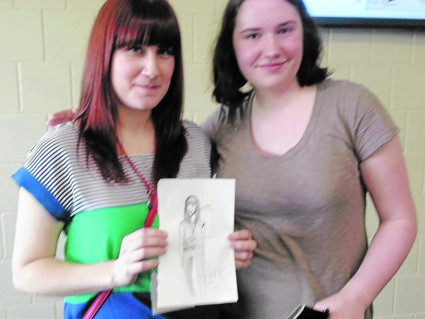 Zoe Burau, right, an eighth grader from Chaska, drew a picture of popular graphic novelist Faith Erin Hicks during Hicks' presentation at Teen Lit Con at Sibley High School, Mendota Heights, May 7, 2016. (Courtesy photo)