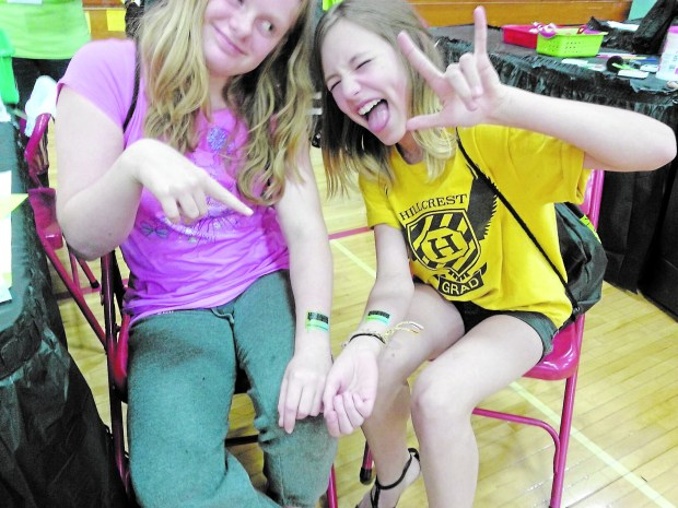 Eva Berglund, left, and Olive Trembley, sixth-graders from Bloomington, show off temporary tattoos during Teen Lit Con at Sibley High School, Mendota Heights, May 7, 2016. (Courtesy photo)