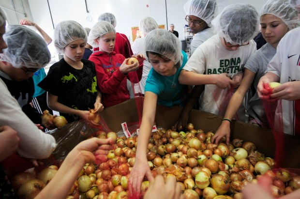 Kids packed bags of onions as one hundred fifth graders from Edina's Normandale Elementary School volunteered at Second Harvest's packing facility in Golden Valley, Mn. on  December 21, 2012.   (Pioneer Press: Scott Takushi)