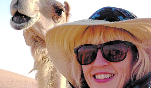 Alison McGhee seems to be sharing a joke with a camel in Sharjah, United Arab Emirates, when she attended the International Reading Festival there in late April. (Courtesy photo)