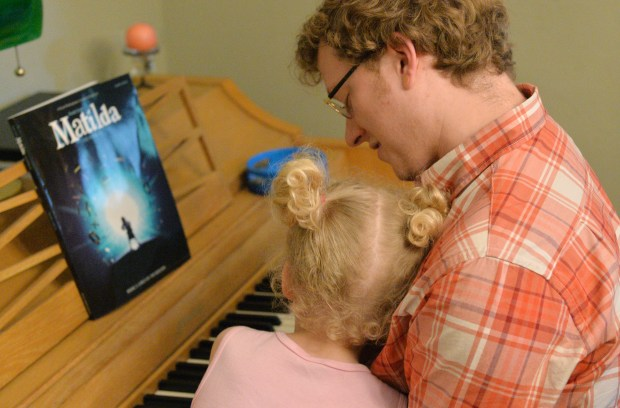 """H rests her head on Dave Edwards' chest as he plays the piano. H loves to sing and knows all the words to all the songs in the musical """"Matilda."""" (Pioneer Press: John Autey)"""