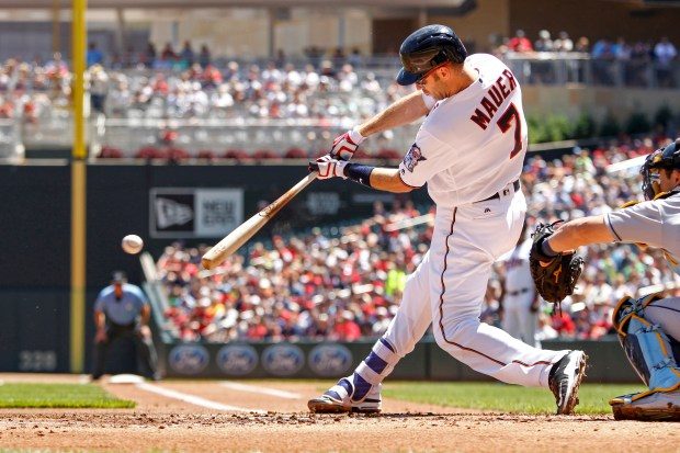 Minnesota Twins designated hitter Joe Mauer hits an RBI-single against the Tampa Bay Rays in the first inning. (AP Photo/Bruce Kluckhohn)