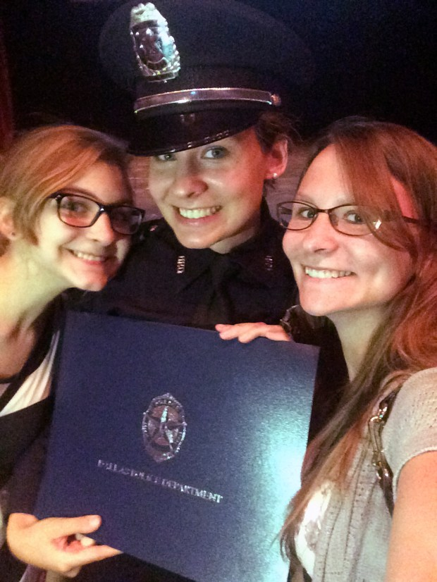 This June 10, 2016, photo provided by Katrina Schwarz shows Gretchen Rocha, center, during her graduation from the police academy at El Centro College in Dallas with her sisters Ingrid Bayer, left, and Katrina Schwartz. (Katrina Schwartz via AP)