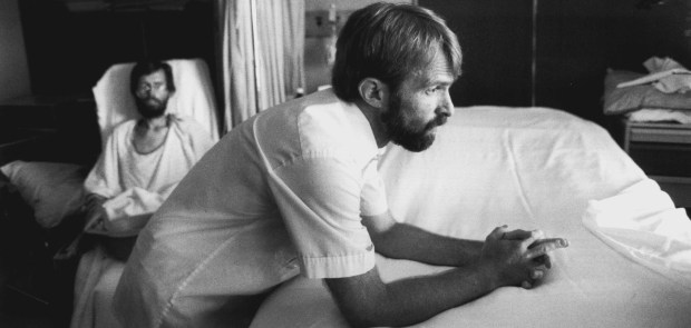 Bert Henningson rests a moment after changing Dick Hanson's soiled sheets, while Hanson waits in a wheelchair. Henningson, who is suffering the early symptoms of AIDS, tires easily. (Pioneer Press: Jean Pieri)