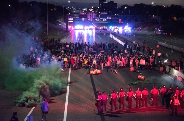 Police shoot smoke rounds after telling protesters to move off Interstate 94 near the eastbound Dale Street exit in St. Paul just before 10 p.m. Saturday, July 9, 2016. Shortly after, the line of police in riot gear moved back about half a block and continued to tell the protesters to leave. Traffic on the interstate was closed in both directions by a large group protesting the police shooting of Philando Castile, who was killed Wednesday night in Falcon Heights. (Pioneer Press: Andy Rathbun)