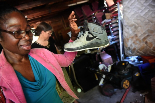 Florence Matadi, mother of Olympic runner Emmanuel Matadi who is competing for Liberia in the 2016 Summer Olympics, shows her son's shoe which survived the fire that burned down her house. Florence is overcoming many hardships Wednesday, August 11, 2016, including a house on 1325 Arkwright that burned down in 2013. Emmanuel had left the house that morning to make a college visit to Mankato. (Pioneer Press: Jean Pieri)