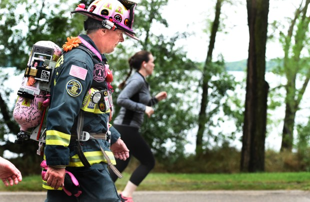 """""""We're gonna crush cancer,"""" said retired firefighter Dale Emmerich from Dane County, Wis., as he walks around Lake Harriet in Minneapolis on the first day of the Susan G. Komen Twin Cities 3-Day 60-mile walk Friday, Aug. 19, 2016. (Pioneer Press: Jean Pieri)"""