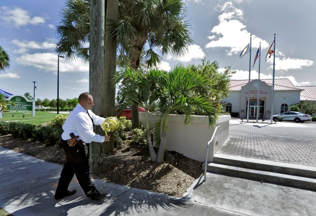 "Punta Gorda Police Dept. Det. J. Davoult takes down crime scene tape outside Public Safety Complex Wednesday, Aug. 10, 2016, in Punta Gorda, Fla. Police say an officer accidentally shot a woman to death during a citizen's academy ""shoot/don't shoot"" exercise Tuesday evening. (AP Photo/Chris O'Meara)"