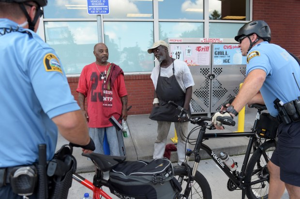 """Bicycle patrol officers Jason Bain, right, and David Ratley ride through the Midway neighborhood near Snelling and University Avenues, stopping to talk to Lee Pearse, left, and Ricky """"CleanUp"""" Fortune in the CVS parking lot, in St. Paul, August 17, 2016. (Pioneer Press: Scott Takushi)"""