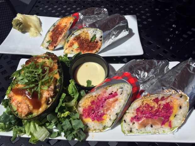 August 11, 2016 photo of (Front to back) a salmon, sotarito with mango, purple cabbage, tempura flakes and coconut mango sauce ($10.75) with a side of snow crab stuffed avocado and spicy tuna sotarito ($10.75) at SotaRol in Minneapolis. (Pioneer Press: Nancy Ngo)