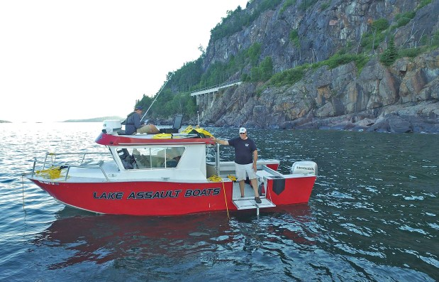 Tom Crossmon of Hermantown and others use an ROV to search for Locomotive 694 in Lake Superior in July 2016 near Marathon, Ontario. The 694 crashed into the lake in 1910 after hitting a rockslide on the railroad tracks that traverse the rock face in the background. (Photo courtesy of Tom Crossmon)