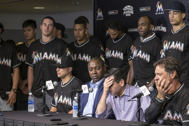 David P. Samson, center, president of the Miami Marlins, covers his face during press conference to announce the death of Marlins pitcher Jose Fernandez. Fernandez, the ace right-hander for the Miami Marlins who escaped Cuba to become one of baseball's brightest stars, was killed in a boating accident early Sunday morning. Fernandez was 24. (AP Photo/Gaston De Cardenas)