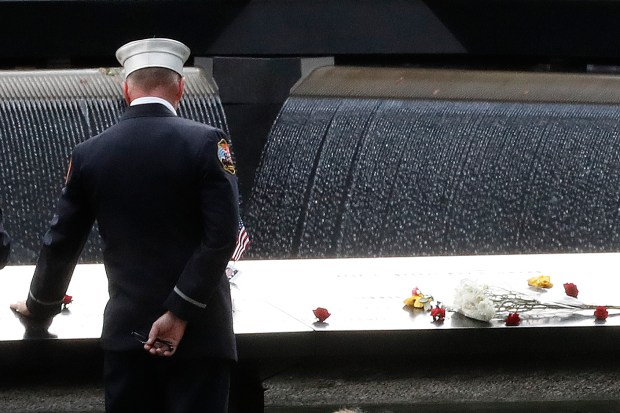 A firefighter touches the names of the firefighters who died in the attacks carved in the south pool during 15th anniversary ceremony of the attacks of the World Trade Center at the National September 11 Memorial, Sunday, Sept. 11, 2016, in New York. (AP Photo/Mary Altaffer)