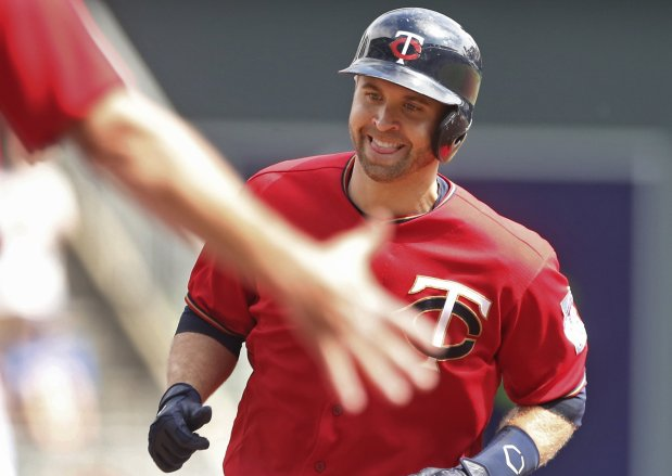Minnesota Twins' Brian Dozier smiles as the third base coach reaches out to congratulate him as he jogs the base path on a solo home run off Kansas City Royals pitcher Ian Kennedy in the first inning of a baseball game Monday, Sept. 5, 2016, in Minneapolis. (AP Photo/Jim Mone)