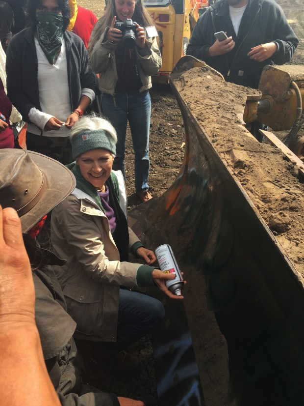 """In this Tuesday, Sept. 6, 2016 photo, Green Party presidential candidate Jill Stein prepares to spray-paint """"I approve this message"""" in red paint on the blade of a bulldozer at a protest against the Dakota Access Pipeline in the area of Morton County, N.D. Morton County Sheriff Kyle Kirchmeier said Tuesday that authorities plan to pursue charges against Stein. (Alicia Ewen/KX News via AP)"""