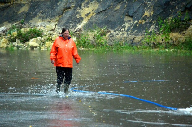 A woman who was helping with the sand-bagging operation at the Faribault Cheese Cave, in Faribault, Minn., walks through the water on Thursday, Sept. 22, 2016. Heavy rain has flooded homes, closed major highways, stranded motorists and derailed a train in several Midwestern states. (Brad Phenow/Daily News via AP)