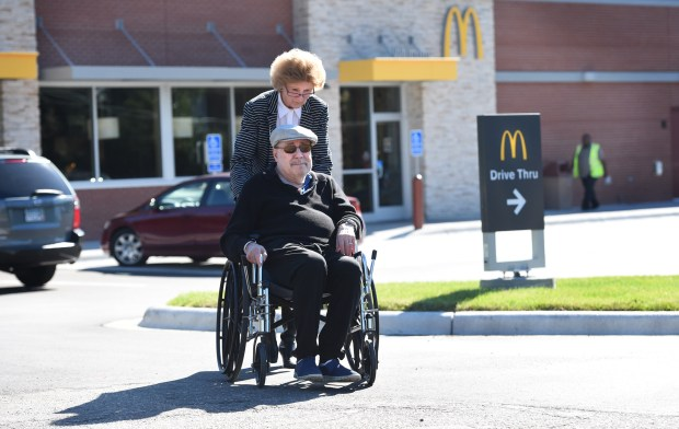 """It takes somebody to push me and to open the door,"" said Vic Grossman, aided by Nancy Weinand at the McDonald's franchise on West Seventh Street in St. Paul on Sept. 14, 2016. Grossman and others have sought to persuade the franchise owner of the recently-rebuilt McDonald's to install an automatic door opener. (Pioneer Press: Jean Pieri)"