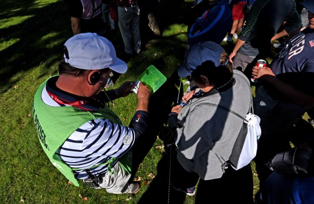 Ryder Cup cell phone policy enforcement worker Mark Ehlenz of Stillwater, Minn., issues a claim check to a woman whose camera he confiscated at Hazeltine National Golf Club in Chaska, Minn., Saturday, Oct. 2, 2016. The woman, who was taking pictures within 100 yards of players on the course, refused to provide her name.(Pioneer Press: Dave Orrick)